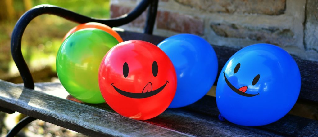 Balloons on a bench outside.