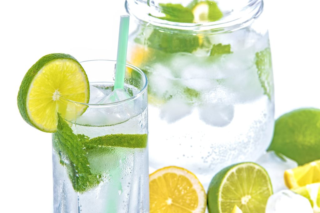 Limeade cocktail with lime pieces.